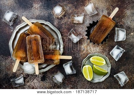 Rum and coke cocktail popsicles with lime juice. Cuba libre homemade frozen alcoholic paletas - ice pops. Overhead flat lay top view copy space