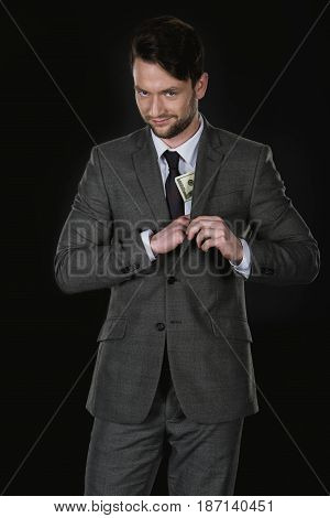 Young Sly Businessman With Dollar Banknotes In Pocket Isolated On Black
