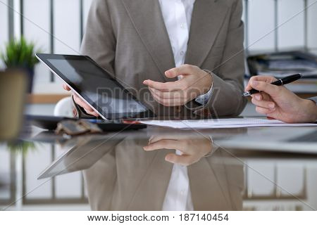 Group of business people or lawyers at meeting  discussing contract papers. Woman pointing into touch pad computer monitor.