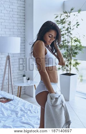 Seductive young female. Attractive young woman in underwear keeping hand in hair and eyes closed while standing in the bedroom