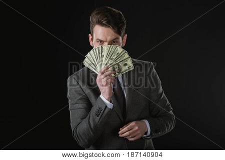 Young Businessman Holding Dollar Banknotes Fan Isolated On Black