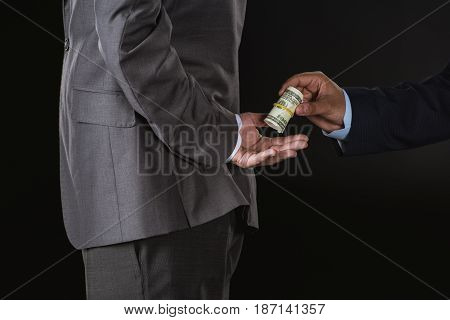 Close-up Partial View Of Businessman Giving Money And Bribing Business Partner Isolated On Black
