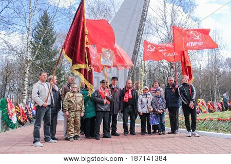 Kirishi, Russia - 9 May, A group of people are photographed under red flags, 9 May, 2017. Laying wreaths and flowers in memory of the fallen at the Eternal Flame.