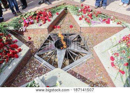 Kirishi, Russia - 9 May, Eternal fire strewn with coins, 9 May, 2017. Laying wreaths and flowers in memory of the fallen at the Eternal Flame.