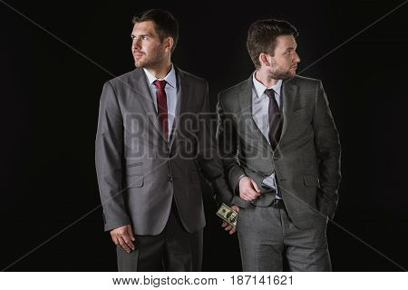 Businessman Giving Money And Bribing Business Partner Isolated On Black