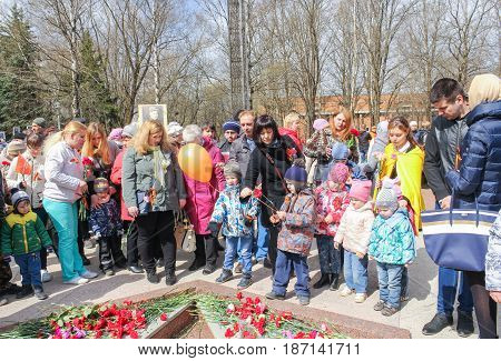 Kirishi, Russia - 9 May, People with children near the Eternal Flame, 9 May, 2017. Laying wreaths and flowers in memory of the fallen at the Eternal Flame.