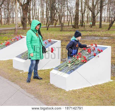Kirishi, Russia - 9 May, Mother and son at a memorable plate, 9 May, 2017. Laying wreaths and flowers in memory of the fallen at the Eternal Flame.
