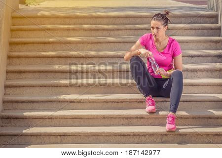 Fitness runner woman sitting on staircase. Athlete girl taking a break during run to hydrate during hot summer day. Healthy active lifestyle.