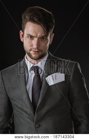 Portrait Of Serious Businessman With Joker Cards In Pocket Isolated On Black