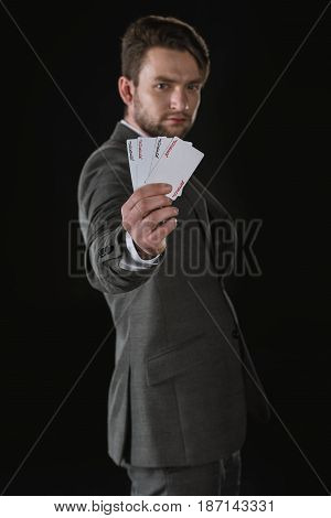 Side View Of Businessman Showing Joker Cards Isolated On Black