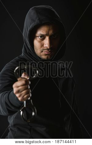 Young African American Robber In Zoodie And Manacles Isolated On Black