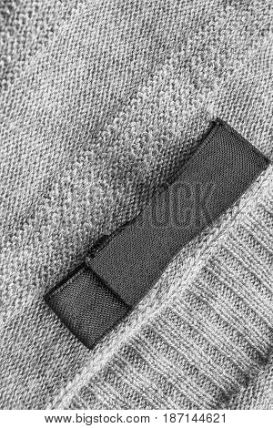 Black clothes label on gray wool knitted background closeup