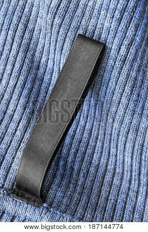 Blank black clothes label on blue knitted background closeup