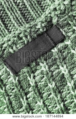 Blank clothes label on green wool knitted background