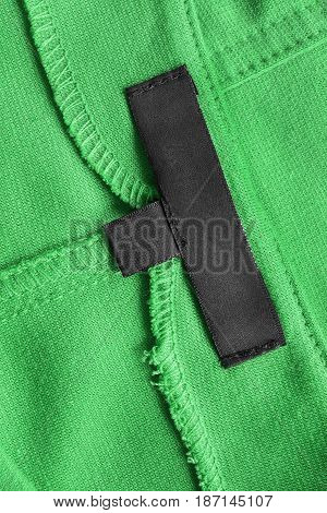 Blank black clothes label on green cotton as a background