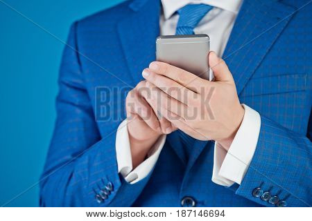 businessman or man with mobile or cell phone in formal suit or classy outfit on blue background