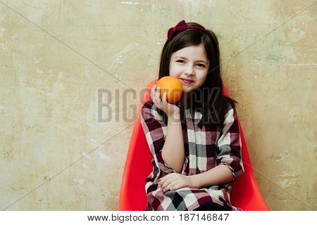 Cheerful Girl With Orange In Hand Smiling In Plastic Chair