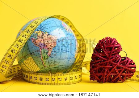 Concept of distant relationship: earth globe tied around with measuring tape next to handmade red heart decorated with a ring on a top yellow background isolated