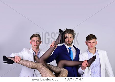 group of people men or businessmen in jacket and female sexy legs in fashionable shoes and tights on grey background love and relations power boss office romance sexual services copy space