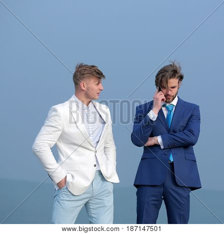 meeting and communication partnership and team work men speaking on mobile phone on blue sky background businessman and employee in outfit outdoor