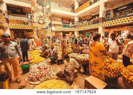 BANGALORE, INDIA - FEB 14, 2017: Flowers traders selling colorful floral garlands inside crowded city market on February 14, 2017. With population 8.52 million Bangalore is 3rd most populous indian city