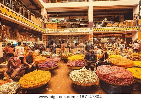 BANGALORE, INDIA - FEB 14, 2017: Flower market and sellers having business of colorful building of city market on February 14, 2017. With population 8.52 million Bangalore is 3rd most populous indian city