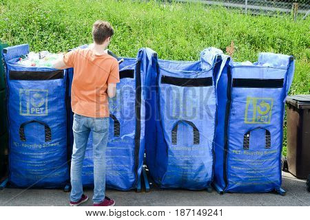 Lugano Switzerland - 9 May 2015: Man throwing pet bottles on the container of a recycling center