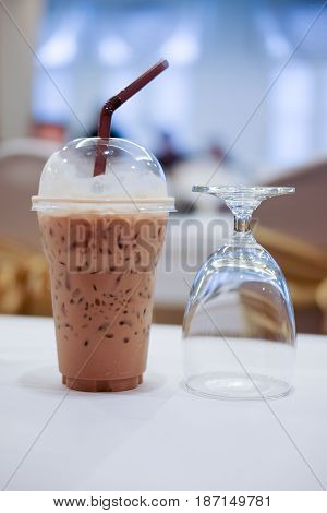 Cold coffee with ice in take away cup and glass of water in the conference room
