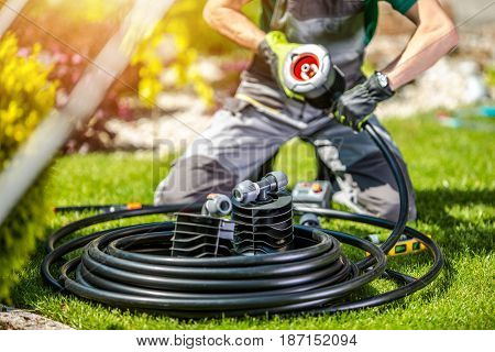 Garden Watering System Building by Professional Garden Systems Technician. Automatic Watering System in the Backyard Garden.