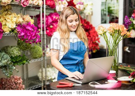 Female Florist Writing On Her Computer