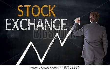 Businessman writes stock exchange on blackboard concept