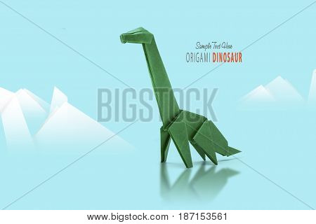 Isolated origami paper green dinosaur on blue mountain background
