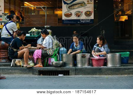 BANGKOK, THAILAND - NOVEMBER 27, 2016: A group of women clean dishes and prepare food to sell on the street in Thailand