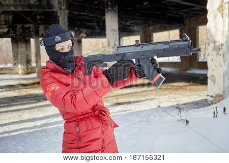 Woman in red jacket aiming with gaming gun outdoor on winter day.