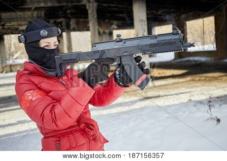 Woman in red jacket and ski mask aiming with gaming gun outdoor on winter day.