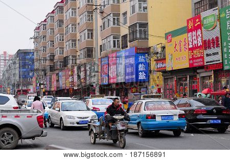 March 28 2017. Zhaodong China. The crowded streets with taxis and cars within the city of Zhaodong China on an overcast day in Heilongjiang province.