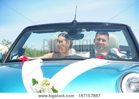 Just married couple driving convertible car