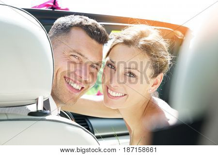 Just married couple sitting in convertible car