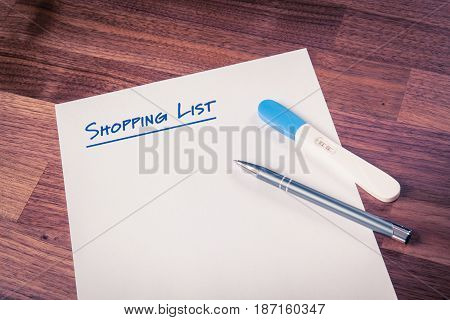 Shopping list notes and pregnancy positive test on wooden table.