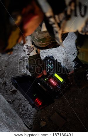 MOSCOW, RUSSIA - JAN 29, 2017: Man inputs activation code into time-bomb case for playing lasertag games outdoor on snowy ground.