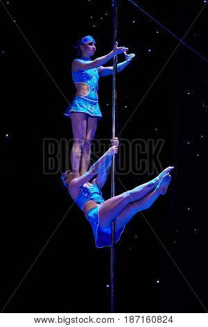 MOSCOW, RUSSIA - FEB 11, 2017: Female duet in blue dresses performs on stage of Korolevskiy concert hall during Pole Dance Show. Concert hall is designed for 750 spectators.