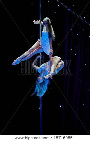 MOSCOW, RUSSIA - FEB 11, 2017: Two female participants perform on stage of Korolevskiy concert hall during Pole Dance Show. Concert hall is designed for 750 spectators.