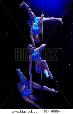 MOSCOW, RUSSIA - FEB 11, 2017: Three girls in blue dresses performs on stage of Korolevskiy concert hall during Pole Dance Show. Concert hall is designed for 750 spectators.