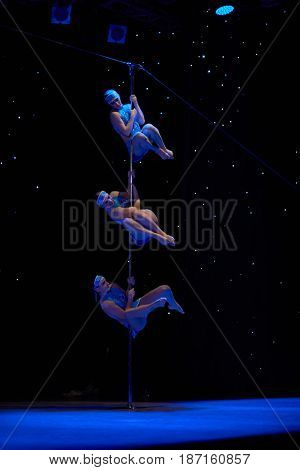 MOSCOW, RUSSIA - FEB 11, 2017: Female trio in blue dresses performs on stage of Korolevskiy concert hall during Pole Dance Show. Concert hall is designed for 750 spectators.