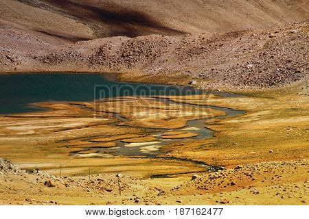 View of Chagor tso - Lake with blue water and Himalayan Mountains over dry bank of Chagor Tso. It is huge lake in Leh Ladakh Jammu and Kashmir India and on way to Pangong Tso -lake