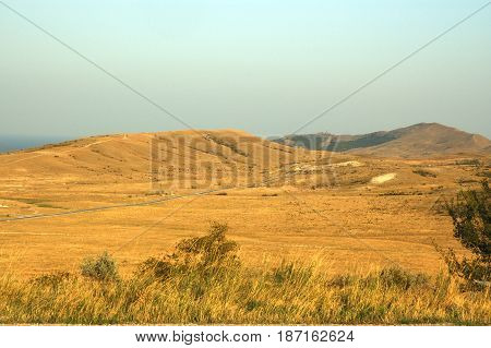 yellow dry grass field blue sea and sky. Karadag mountain National park Black Sea Crimea