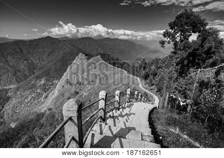 Stair case from foreground to middleground in the frame view of Tarey Bhir point favourite tourist spot. The word 'Bhir' means cliff in the local Nepal language about 10000 feet long path in Sikkim India. Black and white Image.