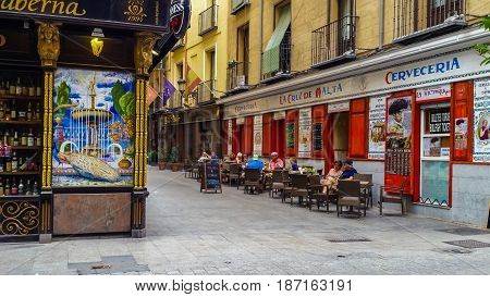 Madrid, Spain - May 17, 2017: Old colorful street with decorative wall tiles and terrace restaurant in central Madrid