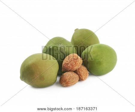 Pile of green olives next to their pits, composition isolated over the white background