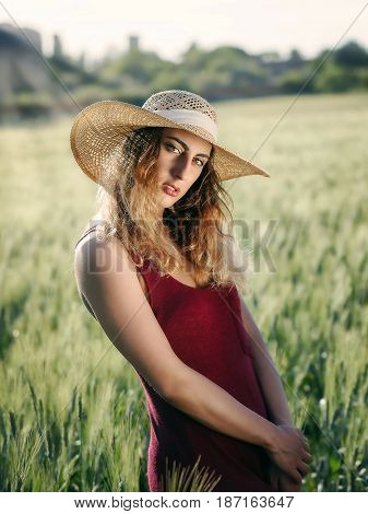 Blonde girl outdoors. With hat and red dress in the wheat field. Backlit.
